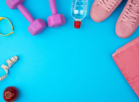 plastic purple dumbbells, sportswear, water, pink sneakers on a blue background, fitness kit, flat lay, copy space