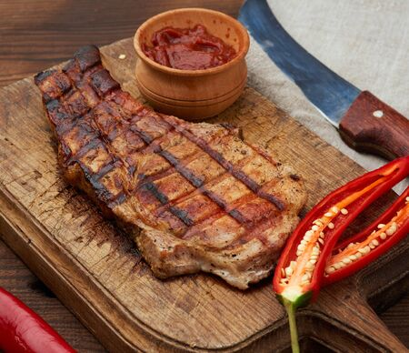 pork fried steak on the rib lies on a vintage brown wooden board, next to fresh red chili peppers, top view Reklamní fotografie