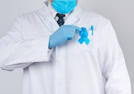 male doctor in a white coat and tie stands. On the pocket pinned a blue ribbon in the shape of a loop, symbol of the fight and treatment of prostate cancer Stock Photo