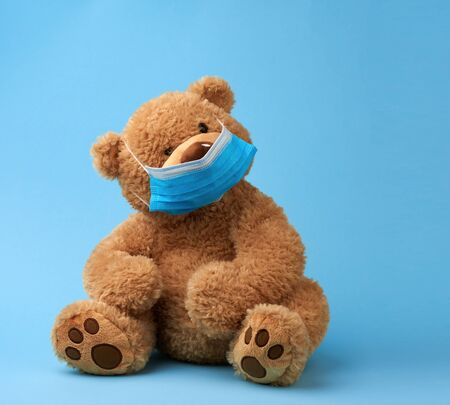 big teddy bear are sitting in blue medical masks on a blue background, concept of protection from respiratory disease, virus, and individual respiratory protection