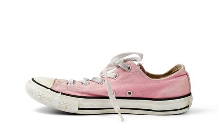 one light pink worn textile sneaker with laces isolated on a white background, side view Stock Photo