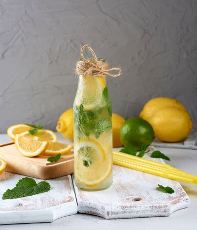 summer refreshing drink lemonade with lemons, mint leaves, lime in a glass bottle, next to the ingredients for making a cocktail
