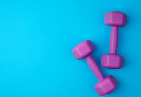 pair of purple plastic dumbbells on a blue background, top view, training equipment