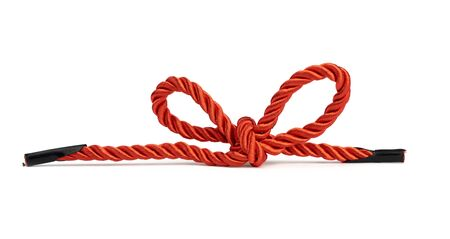 red twisted lace from silk threads is isolated on a white background and tied in a bow, close up