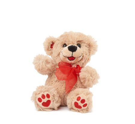 cute little brown teddy bear, toy is sitting on a white background, close up Foto de archivo