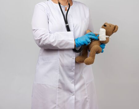 female medic holds brown teddy bear with paw bandaged in white bandage and listens to toy with stethoscope, concept of pediatrics and animal treatment