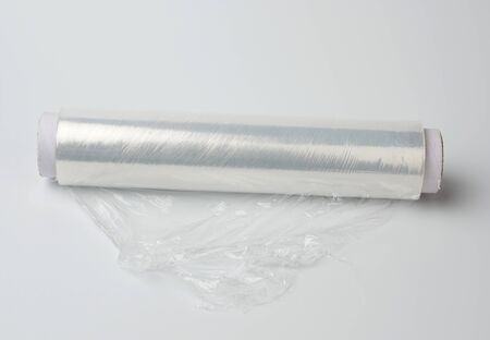 big roll of wound white transparent film for wrapping food, white background, top view