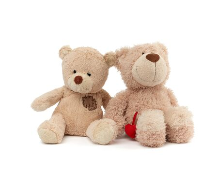 two teddy beige bears sitting huddled together, toys isolated on white background