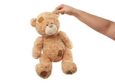 female hand holds the ear of a big beige cute teddy bear with patches, toy is isolated on a white background Foto de archivo