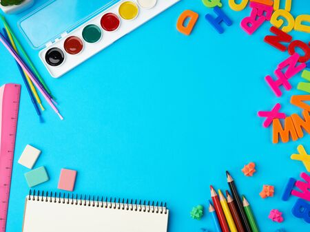 stationery school supplies for creativity and learning on a blue background, top view, empty space in the middle, flat lay