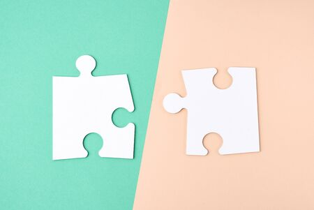 white large blank paper puzzles on a beige green background, top view, copy space