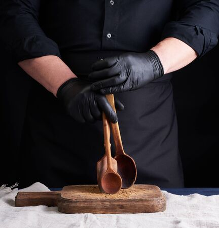 chef in black latex gloves and a black uniform holds wooden vintage spoons in front of him, low key 版權商用圖片