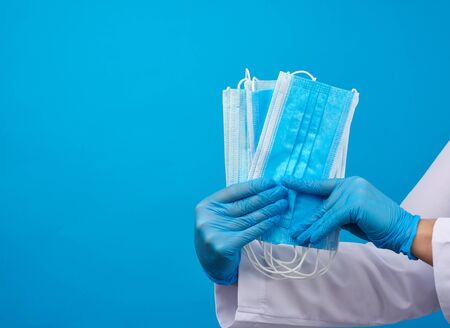 doctor in a white coat, blue latex sterile gloves holds textile disposable medical masks in his hand on a blue background, protective accessory for the respiratory tract from the virus, copy space