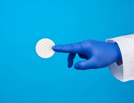 hand hold white cotton round disc for cosmetic procedures on a blue background, close up
