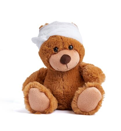 brown teddy bear with a bandaged head in a white medical bandage on a white background, concept of child trauma, headache