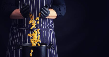 chef in black latex gloves, striped apron pours raw fusilli pasta into a metal pan, cooking process, twisted pasta frozen in the air, copy space Banque d'images
