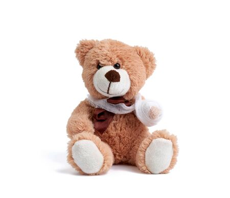 funny vintage brown curly teddy bear with rewound paw with white gauze bandage isolated on white background, concept of injuries in children or animals Stock Photo