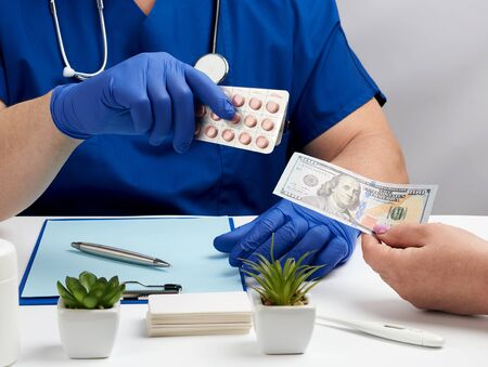 male doctor in uniform and in blue latex medical gloves sits at a table and gives a package of pills to a patient, sale process, bribes