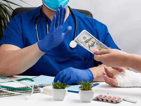 male doctor in uniform and in blue latex medical gloves sits at a table and shows with his hand a gesture of stop, hand with money stretches out from the side, concept of a bribe and expensive payment for services Imagens