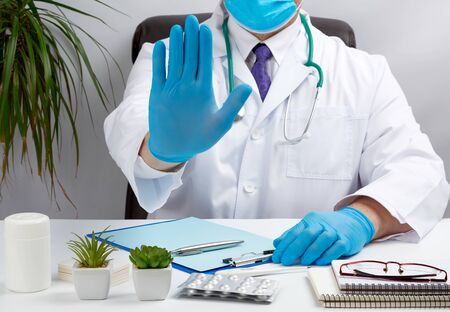 doctor in a white medical coat sits at a table in a brown leather chair and shows with his palm a gesture of stop, calm down and not panic Stock Photo