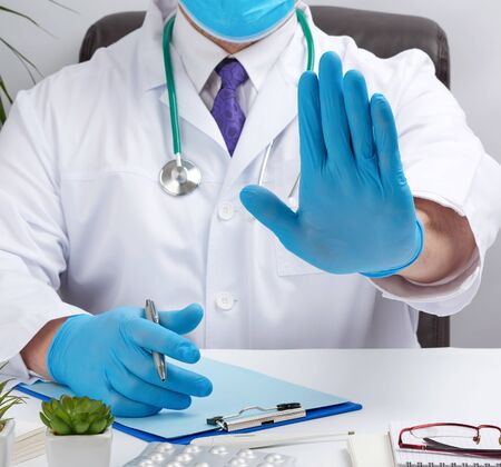 doctor in a white medical coat sits at a table in a brown leather chair and shows with his palm a gesture of stop, calm down and not panic