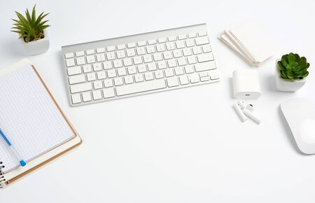 White wireless keyboard, a stack of notebooks, green plants in pots and a mouse, workplace of a freelancer, businessman. White table