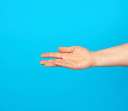hand reaches to the side, gesture that shows holding the item in the palm, blue background
