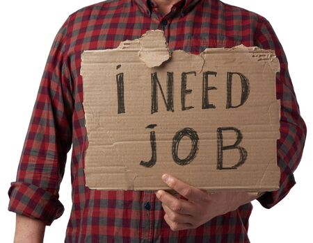 man in a plaid shirt and jeans holds a piece of paper with the inscription i need job, concept of unemployment against the backdrop of the global crisis, fired employee, man is isolated on a white