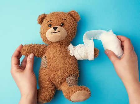funny vintage brown curly teddy bear with rewound paw with white gauze bandage on blue background, concept of injuries in children or animals, copy space Stock Photo