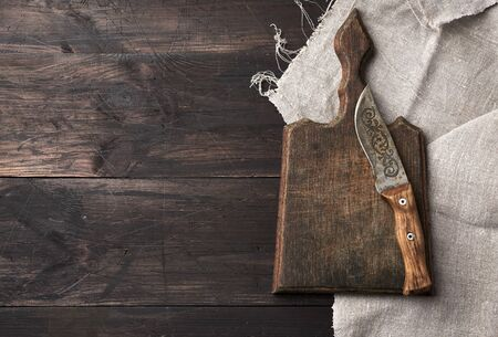 empty old wooden cutting board and vintage knife on the table, top view