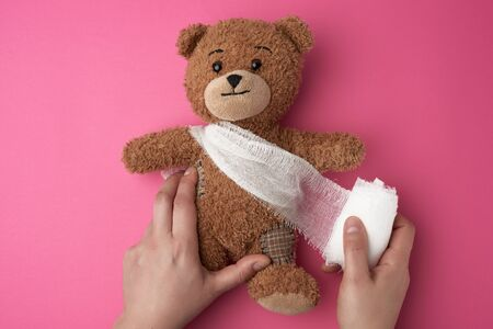 brown teddy bear with bandaged torso with white gauze bandage on a pink background, two female hands are holding a toy Stock Photo