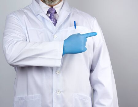 medic man in white coat with buttons, on hands wearing blue sterile gloves, showing hand gesture indicating the subject, white background