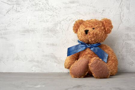 brown teddy bear with a blue bow sits on a white background, place for an inscription