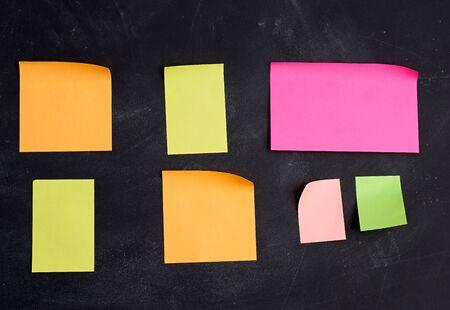 empty paper multi-colored stickers are glued on a black board, place for an inscription Foto de archivo