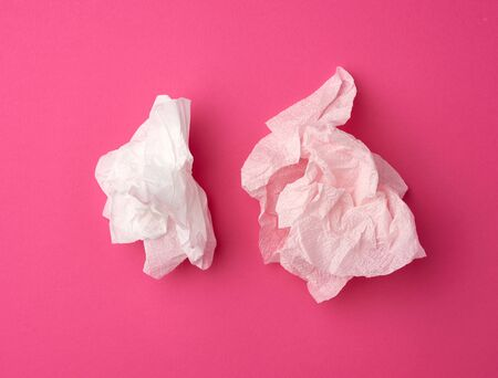 crumpled white paper disposable napkins on a pink background, top view