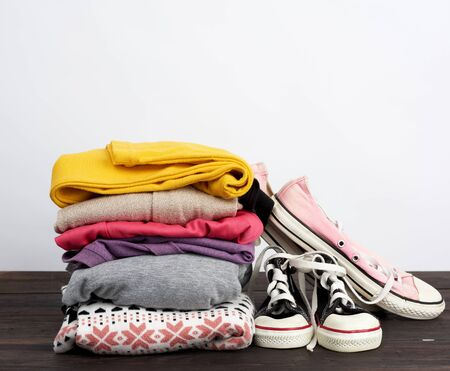 stack of various folded clothes and textile worn cedwas on a wooden table, white background, concept for helping the needy and poor, volunteering