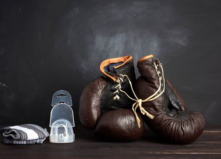 pair of brown leather vintage boxing gloves, silicone cap and wrist bandage, wooden background, sports equipment