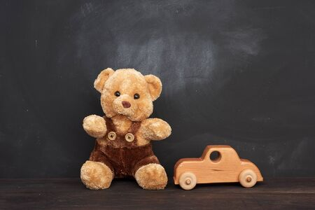 brown teddy bear sits on a brown wooden table and wooden car, behind an empty black chalk board, place for an inscription, back to school