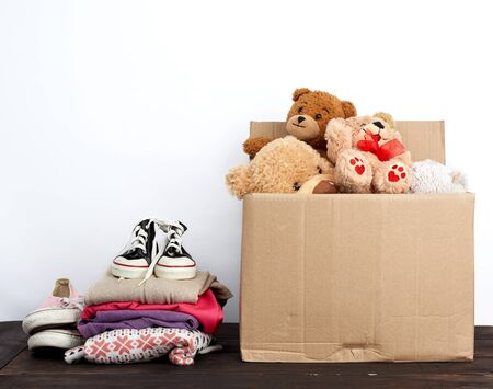 brown cardboard box filled with things and children's toys, concept of moving, volunteering and help