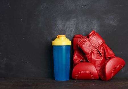 pair of red leather boxing gloves and blue plastic bottle on a black background, sports equipment, copy space