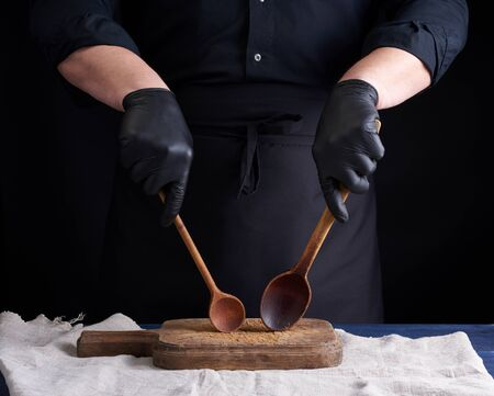 chef in black latex gloves and a black uniform holds wooden vintage spoons in front of him, low key