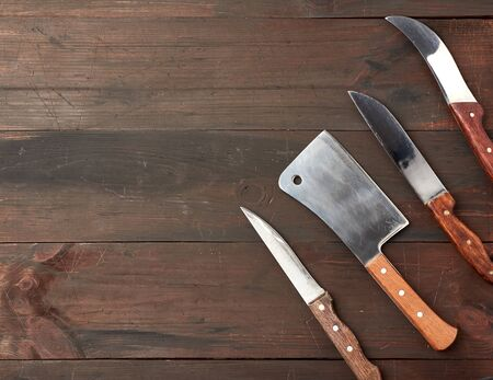 set of different kitchen knives with wooden handles on a brown background from boards, top view Фото со стока