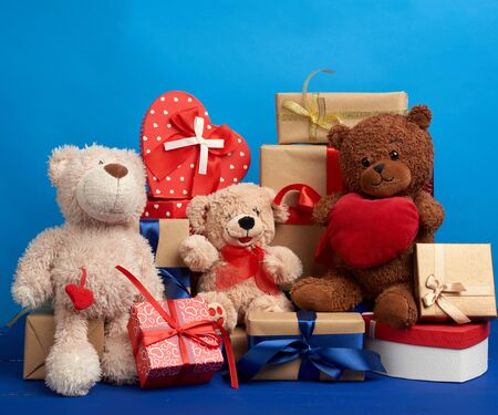 bunch of gifts in boxes tied with silk ribbons and soft teddy bears on a blue background, festive backdrop for birthday, Christmas