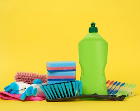 rubber gloves for cleaning, multi-colored sponges, brushes and cleaning fluid in a green plastic bottle on a yellow background Zdjęcie Seryjne