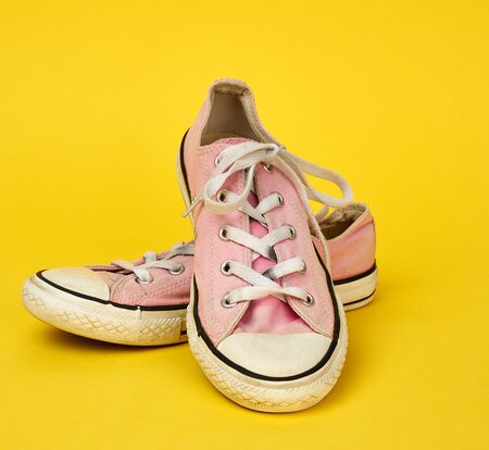 pair of pink very worn textile sneakers with rubber soles on a yellow background