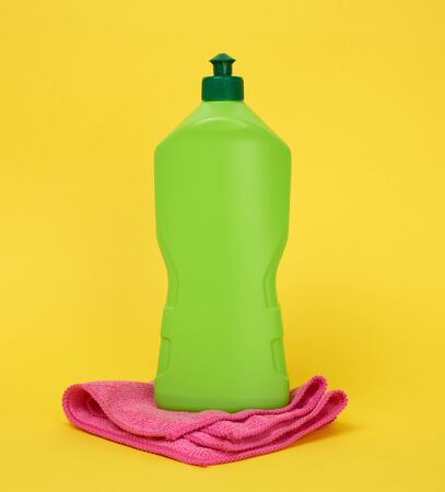 pink kitchen rectangular dishwashing sponges and green plastic bottle with detergent, yellow background
