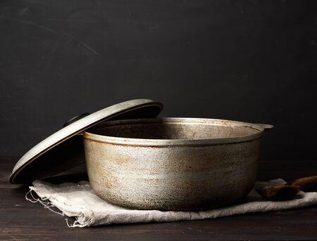 open aluminum old cauldron on a wooden table, kitchen utensils, close up
