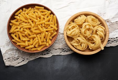 raw fusilli and fettuccine pasta in wooden plates on a black table, top view Banque d'images
