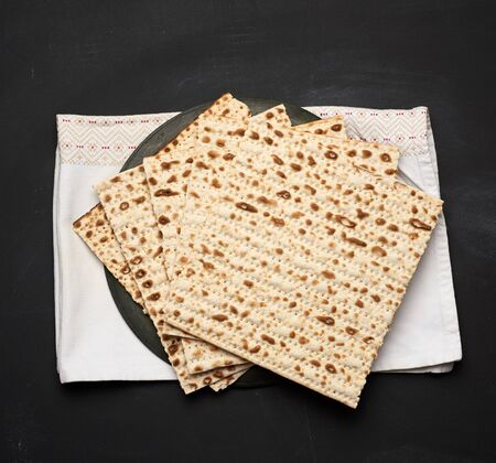 stack of baked square matzo on a black wooden background, top view Banco de Imagens