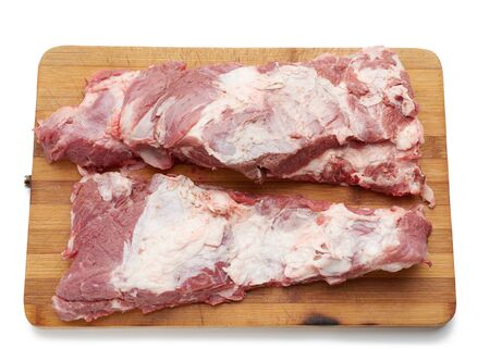 raw strip of pork meat on ribs with layers of fat on a wooden cutting board, top view
